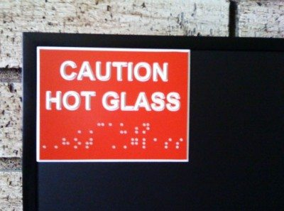 "Image showing a sign that says ""Caution Hot Glass"" in print and braille"