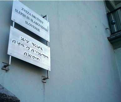 Image showing a print and braille sign on a building but the sign is way too high for anyone to reach