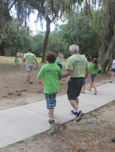 Image of Lou Fioritto (Founder & Co-Owner of Braille Works) walking with his grandson during a company picnic.