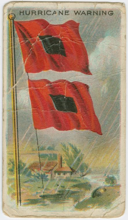 Universally recognized Hurricane Warning flags. Two red flags with black squares in the center and a beachfront home in the background.