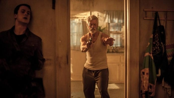 """The Blind Man"" played by Stephen Lang walking through a doorway holding a handgun."