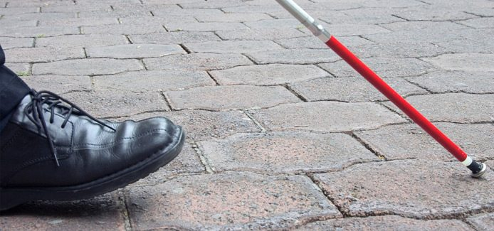 Image showing a close-up view of a persons shoe and White Cane while walking on a sidewalk