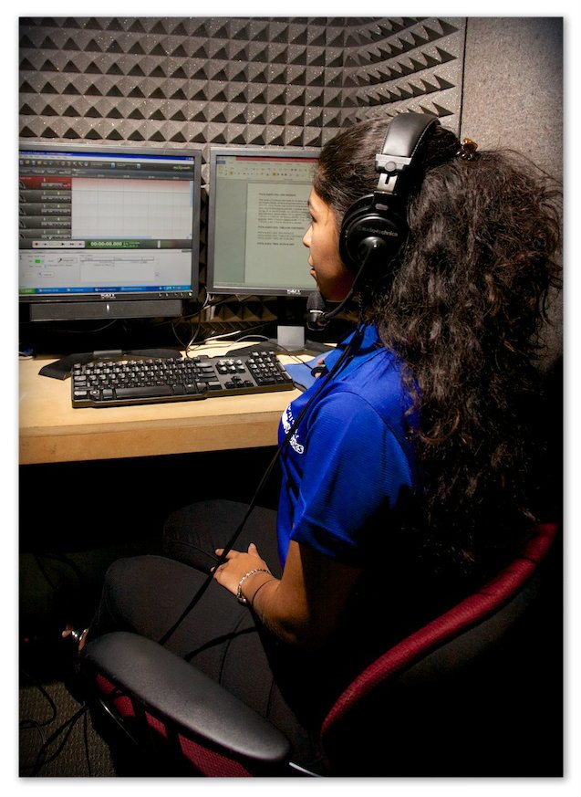 Image showing a Braille Works employee reading and recording audio documents in a recording booth