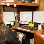 Image of a Braille Works employee sitting at her desk transcribing a document into braille and large print.