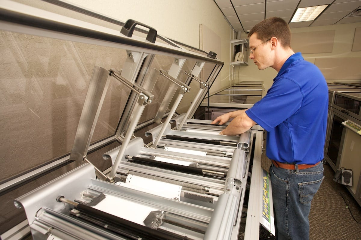 Braille Works staff printing on a top of the line embosser