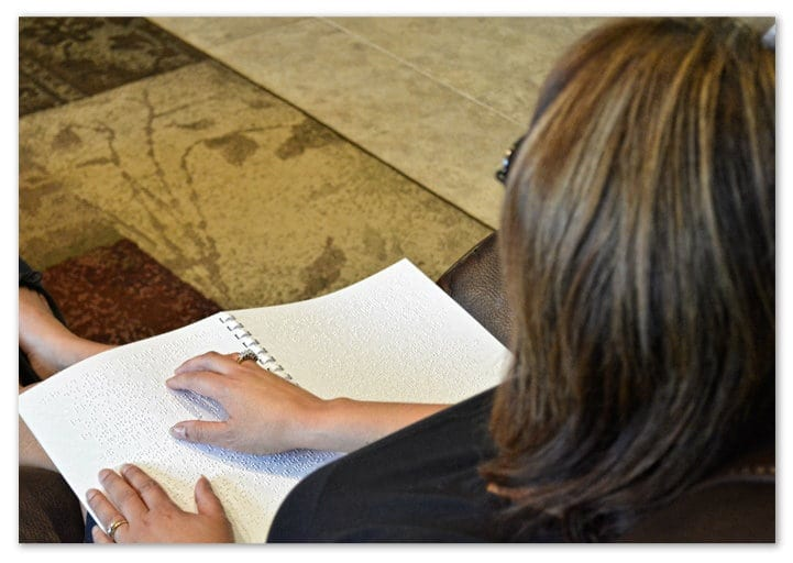 Image of a woman sitting in her living room reading a braille utility statement