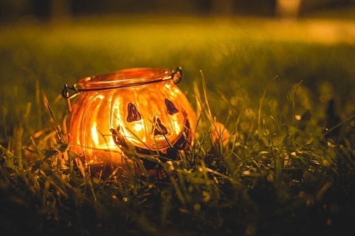a jack o'lantern candle sits in the grass