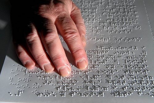 Close-up view of a man reading a Braille document. His hand is over the Braille and lighting is causing the Braille dots to cast shadows.