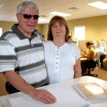 Image showing Lou and Joyce Fioritto standing in front of braille documents with their arms around each other.