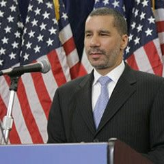 David Paterson standing behind a podium and microphone