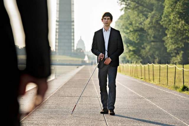 Auggie Anderson walking down waterfront sidewalk with his white-cane during an episode of Covert Affairs