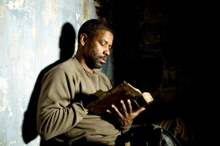 Eli (Denzel Washington) sitting against a wall reading during a scene in the Book of Eli