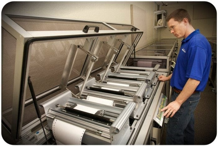 Image showing a Braille Works employee loading braille paper into a braille embosser