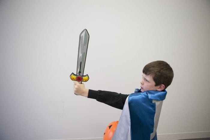 child in a superhero costume with a sword