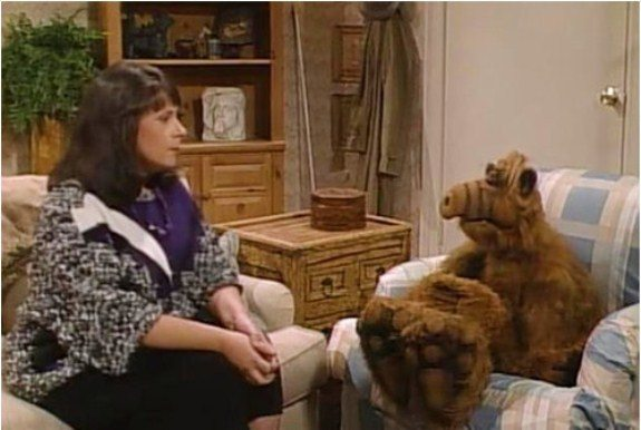 Jody sitting on a couch across from ALF
