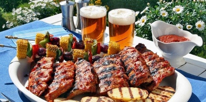 Image showing a plate full of barbecue spare ribs, chicken and veggies with two glasses of beer on the side.