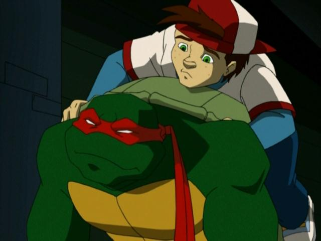 Raphael carrying a kid on his back. The boy helps to orient Raphael after he is blinded during episode of Teenage Mutant Ninja Turtles.