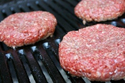 Image showing raw hamburger patties on a grill