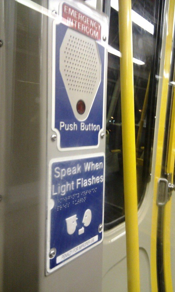 "Subway emergency intercom with the phrase ""speak when the light flashes"" written in print and braille."