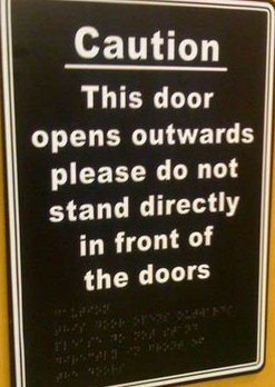 "A print and braille sign that says ""Caution. This door opens outwards, please do not stand directly in front of the doors."""