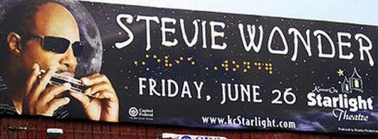 Image of a billboard promoting a Stevie Wonder concert with braille characters spelling his name