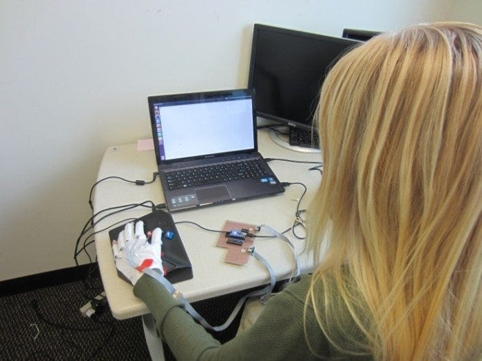 Image showing a young woman sitting in front of her laptop wearing a computing braille glove.