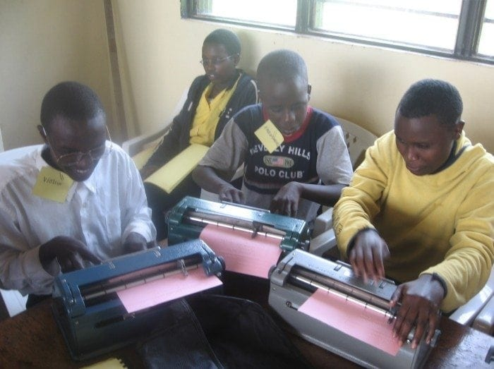 Image showing several students working with Perkins Braillers to create braille documents at the HVP Gatagara School for the Visually Impaired.
