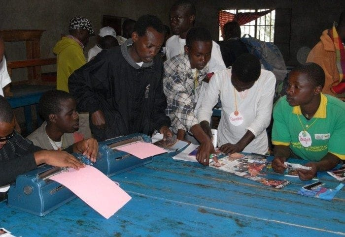 Image showing Eric Niyikiza working on an art project with several boys at Camp BE.