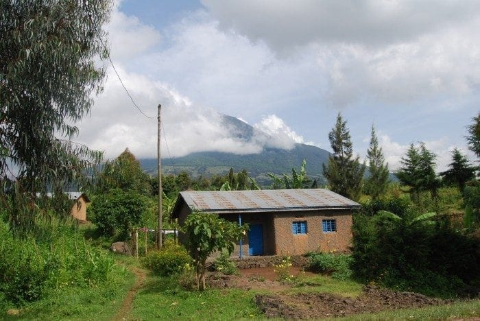Image showing a typical Rwandan house with the Muhabura Volcano in the distant background.