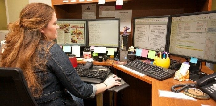 Image showing a Braille Works employee at her desk converting documents to braille and large print formats.