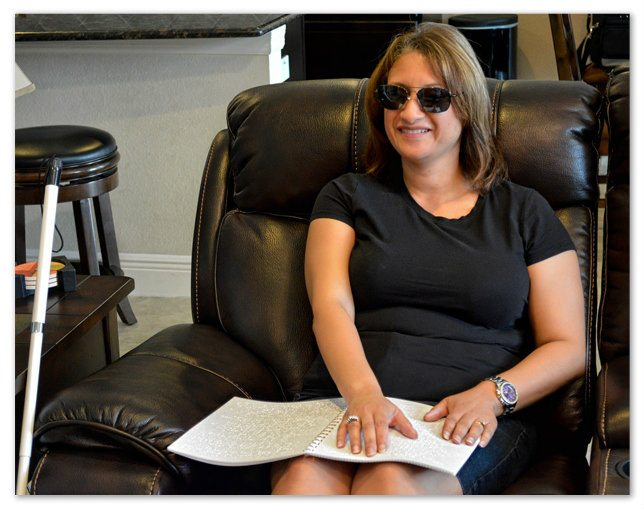 Image showing a woman sitting on her couch reading a braille document by Braille Works.