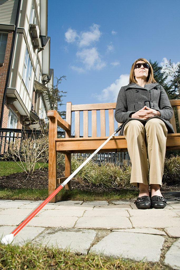 A woman who is blind sitting on a bench with her white cane next to her.