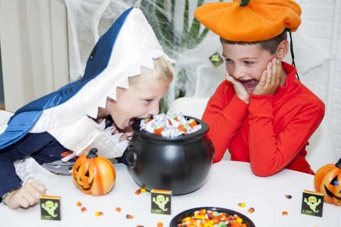 Image showing two young boys in Halloween costumes snacking on candy.