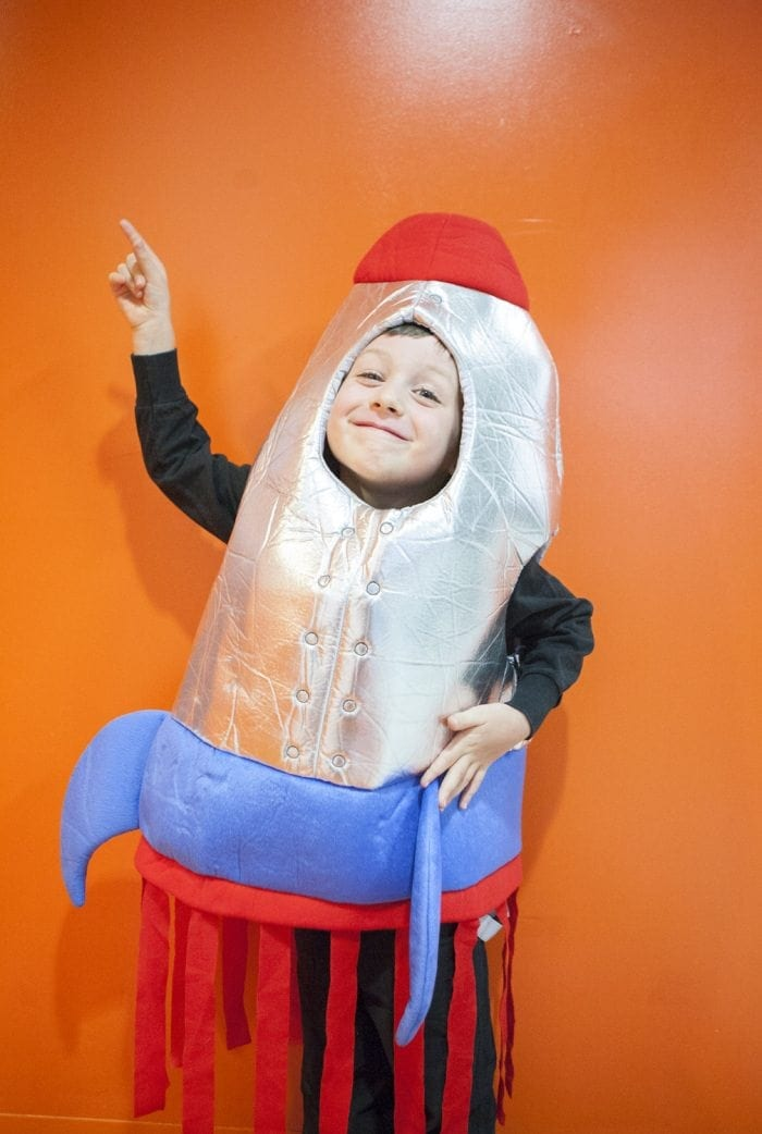 Image showing a young boy wearing a rocketship Halloween costume and pointing upward.