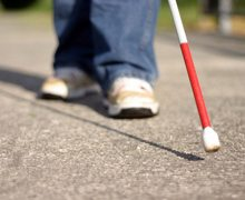 Image showing a close up view of the tip of a white cane while a person is walking down the sidewalk