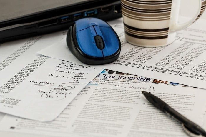 Computer mouse, mug, and pen on top of financial papers