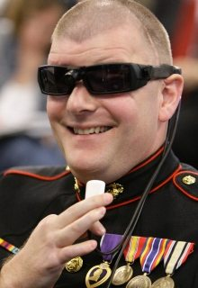 Image of a retired Marine who lost both eyes in an explosion in Iraq demonstrating the BrainPort V100.