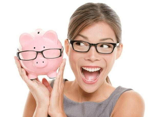 Woman in glasses smiling and holding a pink piggy-bank that also has glasses on.