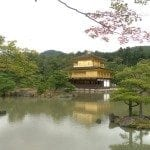 Image showing a calm body of water in Kyoto, Japan with lush trees, rolling hills and the three story Golden Pavilion in the background