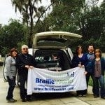 Members of the Braille Works management team holding a Braille Works banner behind a sports utility vehicle.