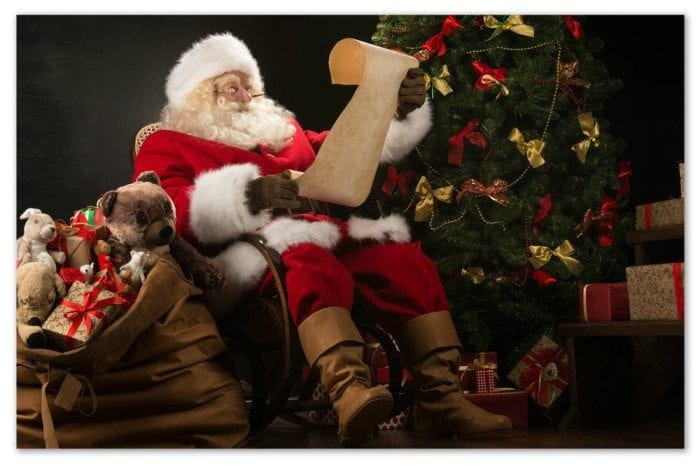 Santa sitting in a chair next to a Christmas tree reading a child's letter.
