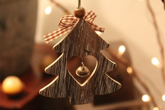 A wooden ornament of a Christmas tree, with a bell in the center of a heart-shaped cutout.