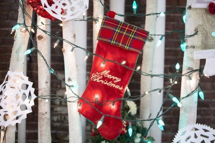 Christmas stocking, lights and paper cut-out snowflakes hanging in a tree