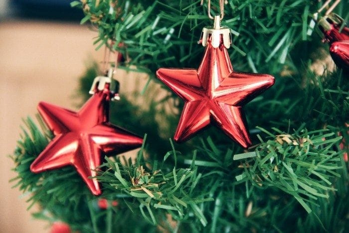 Close-up view of a plastic Christmas tree and two star-shaped ornaments.
