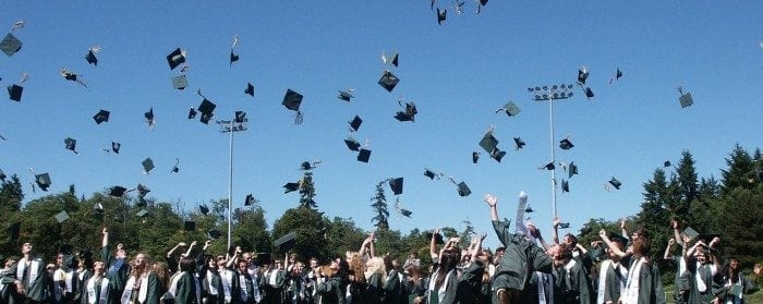 Large group of graduates tossing their caps into the air.