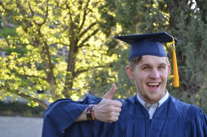 A young man wearing a graduation cap and gown, smiling and giving a thumbs up.