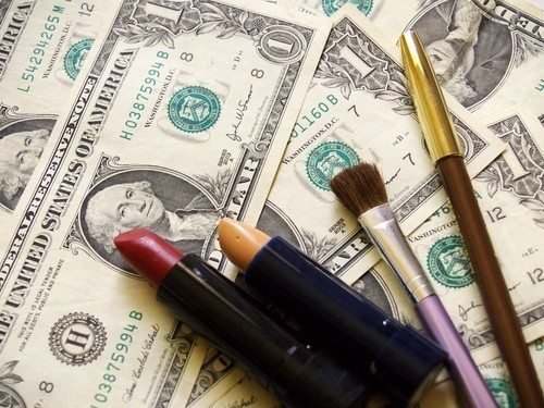 Scattered dollar bills with lipstick and makeup brushes on top