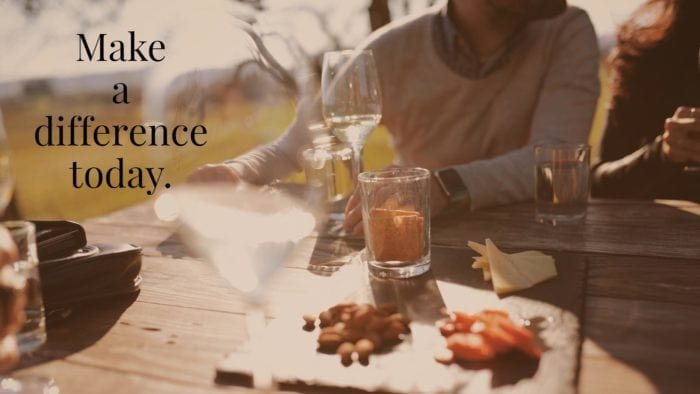"""A table setting with food and drinks, with a person leaning out of view. The words """"make a difference today,"""" are overlaid."""