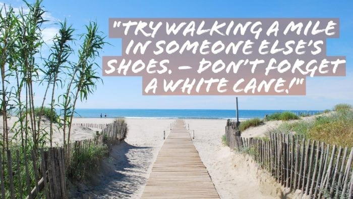 """A walkway in sand heading toward a beach, with the words """"Try walking in someone else's shoes. -Don't forget a white cane!"""""""