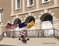 The image of a customs house with the america flag, Gadsden flag, British flag, and a blue Liberty flag.